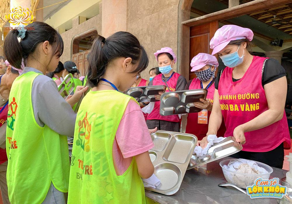Các bạn khóa sinh phụ giúp các cô bác Phật tử Ban hành đường lau khay đựng cơm